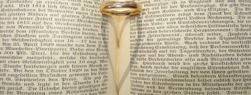 Ring auf Buch witft Schatten in Herzform